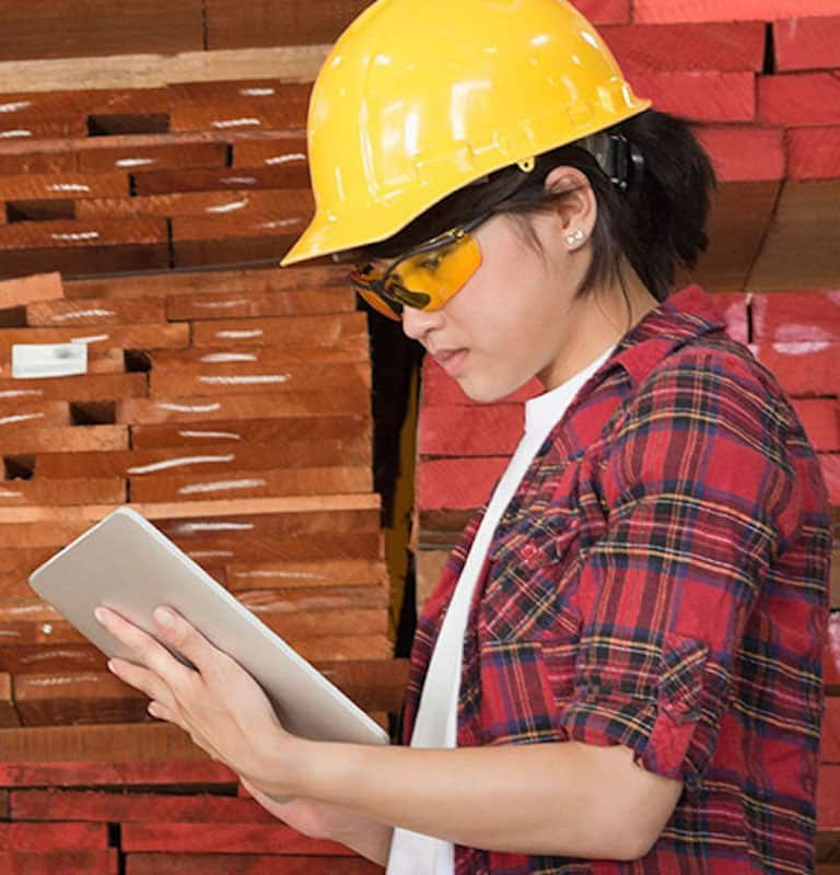woman in a plaid shirt and a yellow hard hat checking a tablet in a warehouse filled with shelves of lumber